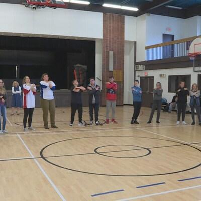 Un groupe d'élèves, en ligne, dans le gymnase d'une école.