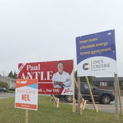 Les pancartes électorales des trois partis sur un terrain.