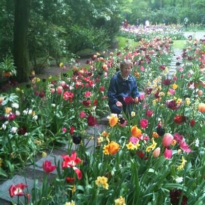 La femme est posée accroupie dans une allée bordée de tulipes.