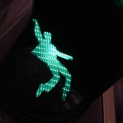 Un feu de signalisation avec une silhouette verte qui se déhanche.
