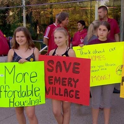 Quatre jeunes filles tiennent des affiches où on peut lire des messages d'opposition au projet de réaménagement de la Place Emery.