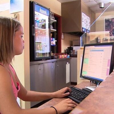 Une jeune femme qui travaille sur un ordinateur.