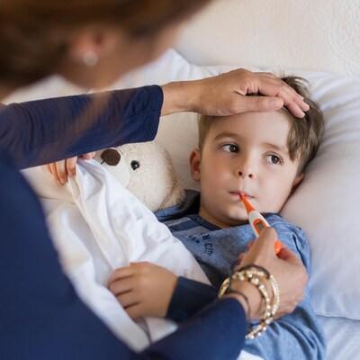 Un enfant malade se fait prendre la température à l'aide d'un thermomètre buccal.