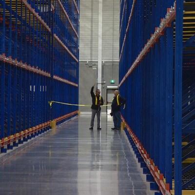 Deux employés de la ville au fond d'un corridor. De chaque côté, les rayons vides de l'entrepôt.