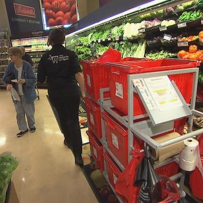 """Une employé prépare des paniers dans un supermarché. Elle porte un uniforme sur lequel il est écrit """"Commande en ligne""""."""
