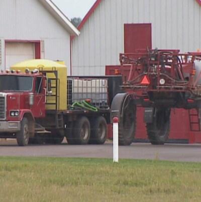 De l'équipement de ferme stationné devant une grange.