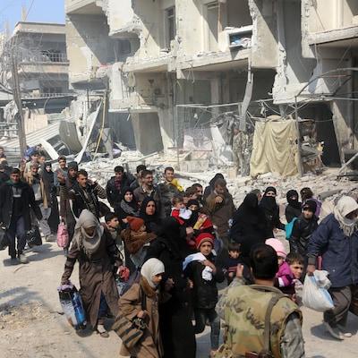 Des Syriens marchent dans la banlieue est de la capitale Damas le 17 mars 2018.