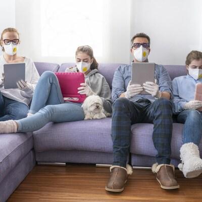 Une mère, un père et deux adolescents portant des masques devant leurs tablettes.