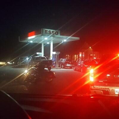 File de voitures dans une station d'essence (soirée).