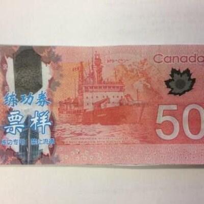 Un billet canadien de 50 dollars avec des idéogrames chinois imprimés de manière visibles.