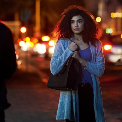Une jeune femme qui marche dans la rue semble avoir peur.