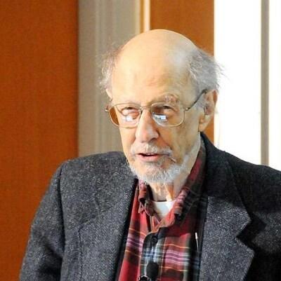 Fernando Corbato, un homme au crâne dégarni et portant des lunettes, un veston gris et une chemise à carreaux rouge.