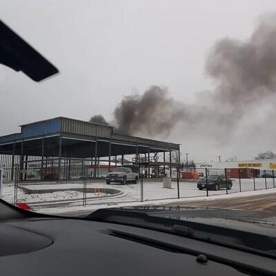 Photo prise par une automobiliste. De la fumée noire s'échappe du toit de la bâtisse.