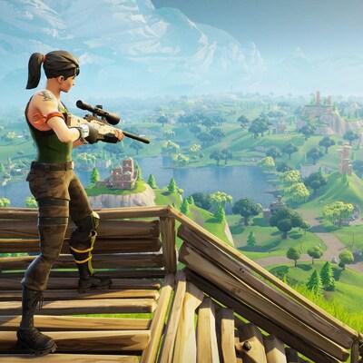 Une capture d'écran du jeu  Fortnite: Battle Royale  montrant un personnage féminin perché au sommet d'un escalier en bois surplombant une vallée luxuriante. Le personnage est équipé d'un fusil de précision.