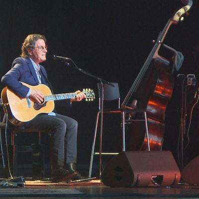 Francis Cabrel seul sur scène entouré de plusieurs instruments.