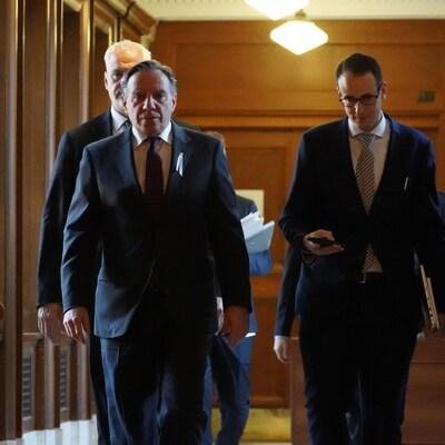 M. Legault et sa garde rapprochée arpentant les corridors de l'Assemblée nationale.