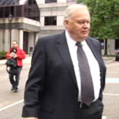 Un homme marche dans un stationnement, suivi de journalistes