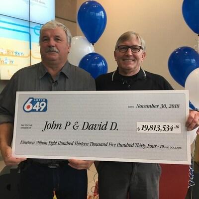 Deux hommes tiennent un gros chèque de plus de 19 millions de dollars.