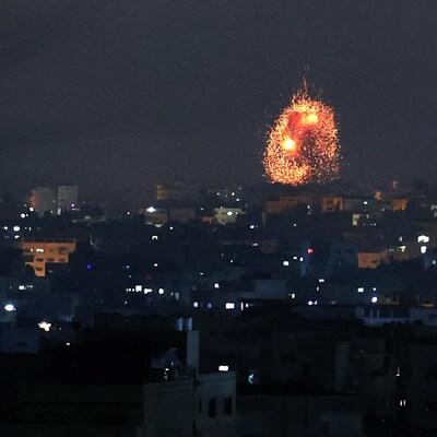 Des immeubles sont illuminés par une explosion.