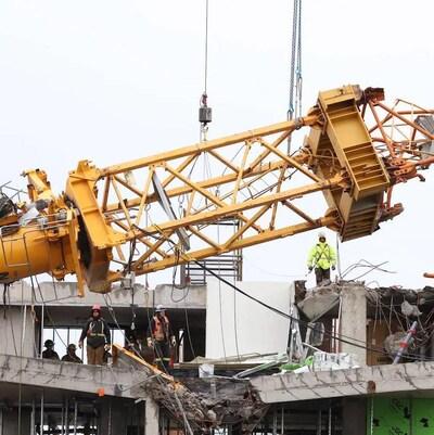 Des câbles soulèvent un morceau de grue au-dessus du toit de l'édifice sur lequel se trouvent plusieurs travailleurs.