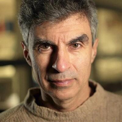 Une photo de Yoshua Bengio regardant directement dans la caméra. Il porte un tricot beige.
