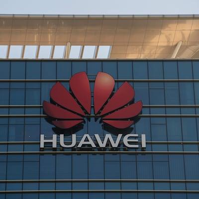 Gros plan sur le logo de Huawei sur la façade d'un gratte-ciel vitré.