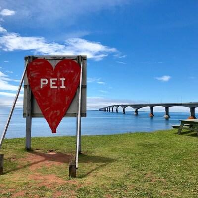 Une affiche avec un coeur « PEI » devant le pont de la Confédération.