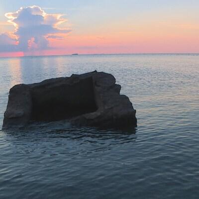 Une pierre au milieu de l'eau avec un ciel dégradé par le coucher du soleil.