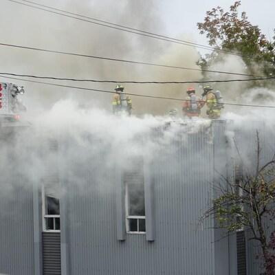 Des pompiers marchent sur le toit de l'immeuble, d'où une épaisse fumée s'échappe.