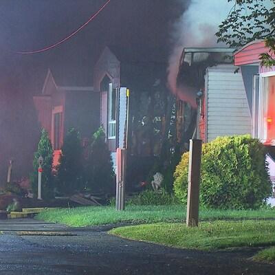 Des flammes se dégagent d'une maison mobile endommagée par un incendie.