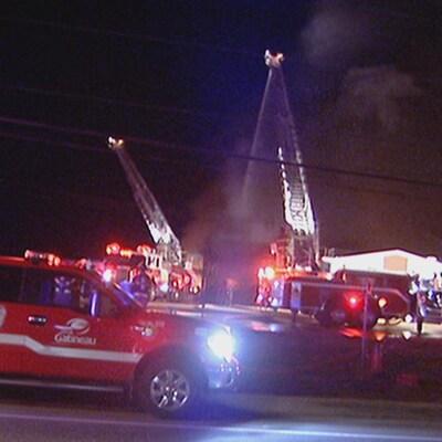 Des camions de pompier et des grandes échelles devant un entrepôt, de nuit.