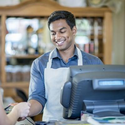 Un jeune homme d'apparence indienne tend un terminal de paiement par carte bancaire à une cliente.