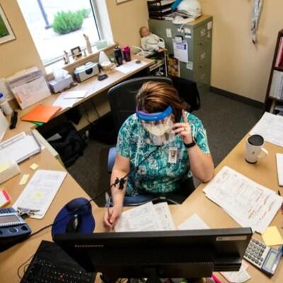 Une employés responsable du traçage de contacts dans son bureau.