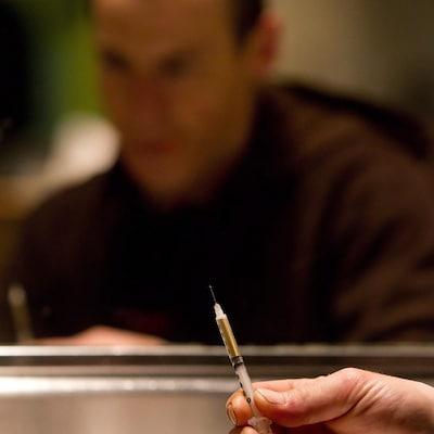 Un toxicomane se prépare à s'injecter de l'héroïne avec une seringue.