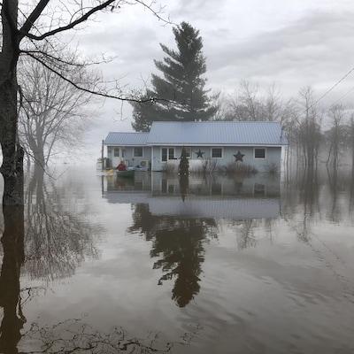 Une femme en canot devant une maison inondée à Maugerville, au Nouveau-Brunswick.