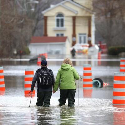 Un homme et une femme se tiennent la main en marchant dans un quartier résidentiel inondé de Gatineau.