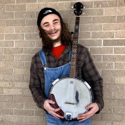 Un jeune homme en salopette souri avec son banjo dans les mains.