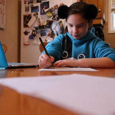 La petite Jacquie Chmilar assise sur une chaise écrit un mot à son bureau