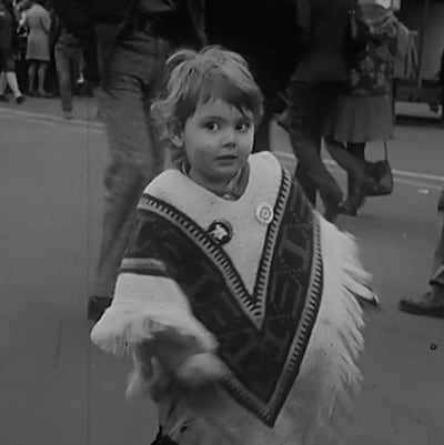 Enfant d'environ deux ans qui danse dans la rue. Il porte un poncho.