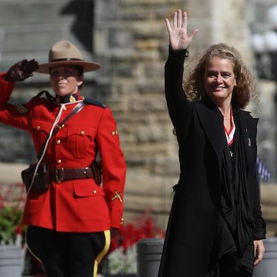 Julie Payette fait un salut de la main en passant devant une agente de la GRC.