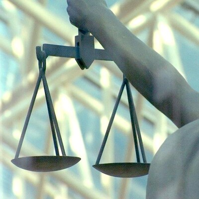Photo d'une statue représentant la justice, prise de dos. Elle tient une balance à bout de bras et ses yeux sont bandés. En arrière plan se trouve une structure métallique ensoleillée.
