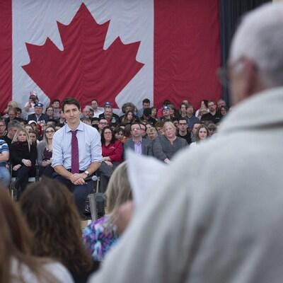 Justin Trudeau écoute la question d'un citoyen debout face à lui.