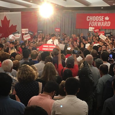 Une foule entoure Justin Trudeau qui est au lutrin.