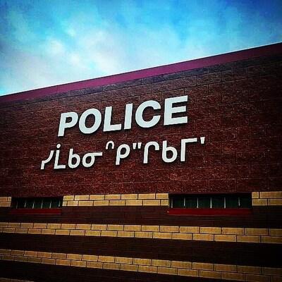 Panneau avec le nom du service de police écrit en anglais et en cri.