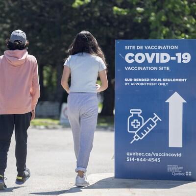 Un homme, un adolescent et une adolescente marchent près d'une pancarte annonçant un centre de vaccination contre la COVID-19.