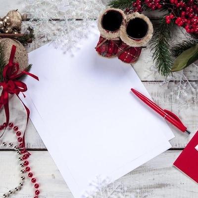 Une lettre de souhaits. Un stylo rouge et une feuille de papier reposent sur un bureau