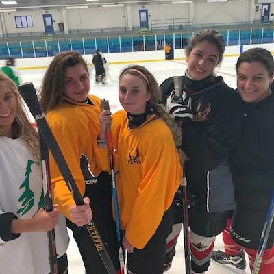 Des joueuses de hockey posent sur une patinoire.
