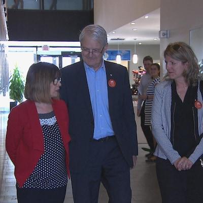 Deux femmes et un homme se promènent dans un couloir.
