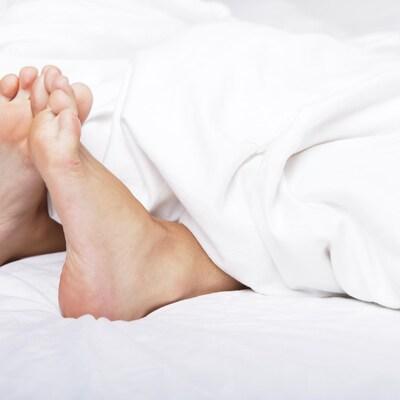 Deux pieds dans un lit dépassent de draps.