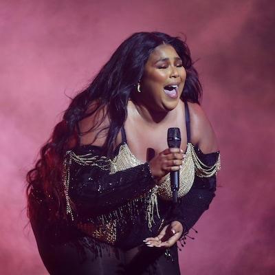 Sur un fond de fumée rose, une femme chante dans un micro.